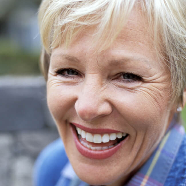 An old woman with white teeth and blonde hair smiling and wearing a sweater
